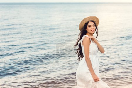 attractive girl in straw hat walking near the sea in summer