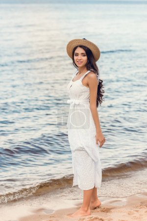 beautiful young woman in straw hat and white dress walking on sea shore
