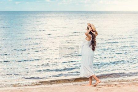 beautiful girl in white dress walking on sandy beach near sea