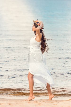 young woman in straw hat and white dress walking on sandy beach