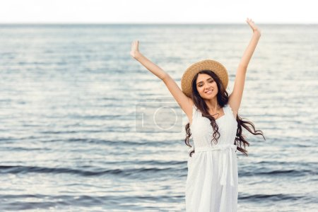 excited brunette girl in straw hat and white dress near the sea in summer