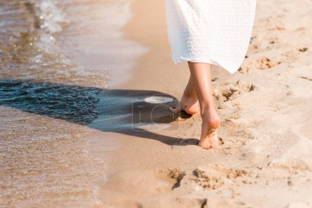 Photo for Partial view of barefoot girl in white dress walking on sandy beach near water - Royalty Free Image