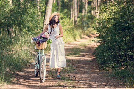 girl in white dress walking with bike and flowers in wicker basket in park