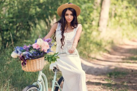 attractive girl in straw hat sitting on bike with flowers in wicker basket in park