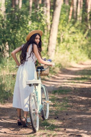 young woman in straw hat and white dress walking with bicycle on trail in forest