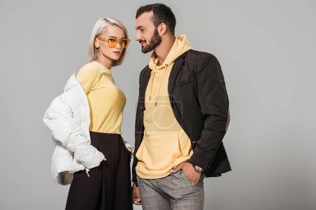 Photo for Stylish couple of models in autumn outfits posing isolated on grey background - Royalty Free Image