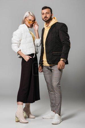 Photo pour Couple à la mode de modèles en tenues d'automne posant sur fond gris - image libre de droit