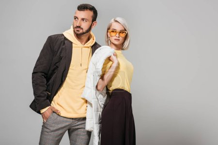 couple of models in stylish autumn outfits posing on grey background