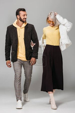 smiling couple of stylish models in autumn outfits on grey background