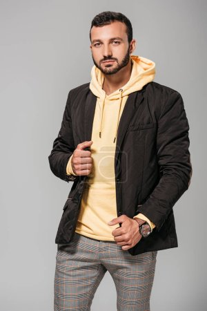 stylish male model in autumn outfit looking at camera on grey background