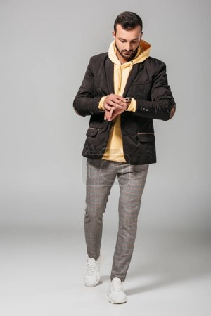 Photo for Fashionable young man in autumn outfit looking at wristwatch on grey background - Royalty Free Image