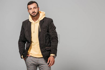 Photo for Confident male model in autumn outfit posing isolated on grey background - Royalty Free Image