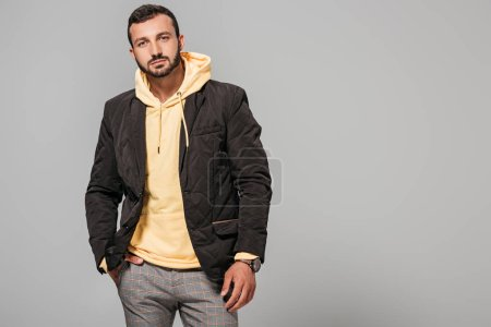 confident male model in autumn outfit posing isolated on grey background