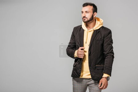 handsome male model in stylish autumn outfit looking away isolated on grey background