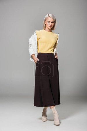 Foto de Modelo de mujer joven seria en elegante traje de otoño con las manos en los bolsillos en fondo gris - Imagen libre de derechos