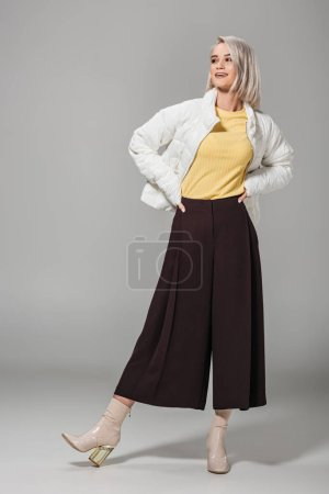 happy fashionable girl in autumn outfit posing with hands on waist on grey background