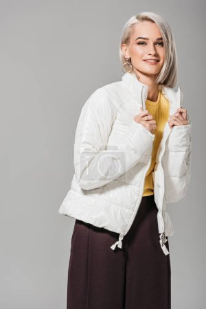 smiling young woman in stylish white jacket posing isolated on grey background