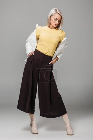 fashionable young woman in stylish outfit posing with hands in pockets on grey background