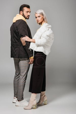 fashionable male and female models in stylish autumn outfits posing on grey background