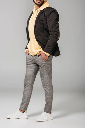 cropped image of man in fashionable autumn outfit posing with hands in pockets on grey background
