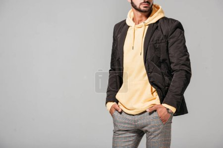 partial view of male model in fashionable autumn outfit isolated on grey background