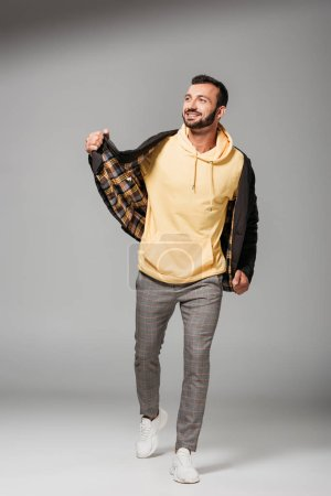Photo pour Heureux jeune homme élégant veste automne posant sur fond gris - image libre de droit