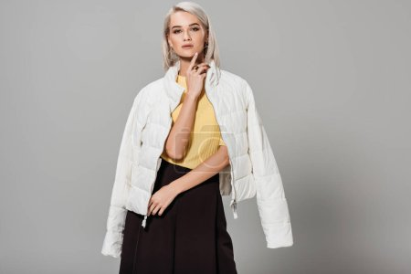 confident young female model in white jacket over shoulders posing isolated on grey background