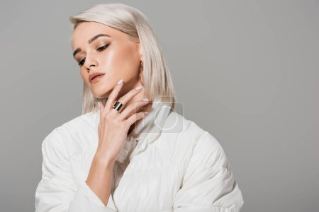 beautiful young woman in stylish jacket looking away isolated on grey background