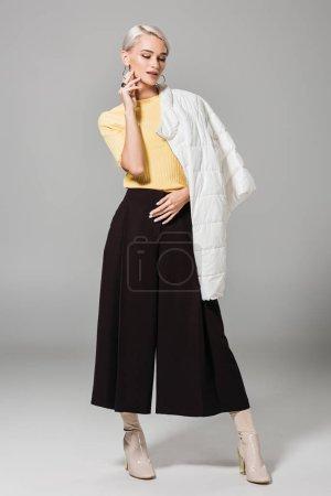 stylish female model posing with jacket over shoulder isolated on grey background