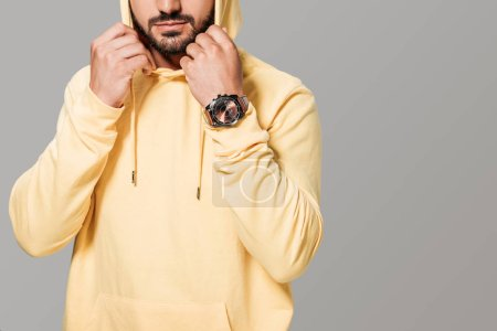 cropped image of bearded stylish man in yellow hoodie isolated on grey background