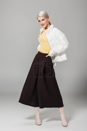 smiling female model in stylish outfit posing with hands on waist on grey background