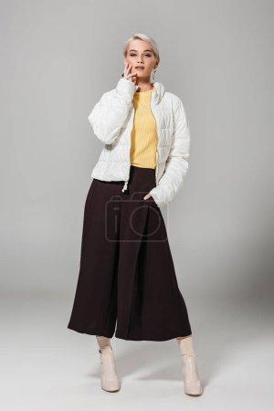 Foto de Atractiva elegante modelo femenino en la chaqueta blanca posando sobre fondo gris - Imagen libre de derechos