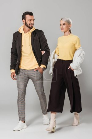 smiling couple of models in stylish autumn outfits on grey background