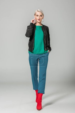 fashionable woman in black jacket and red boots posing on grey background