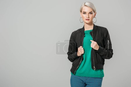 fashionable young female model in black jacket posing isolated on grey background