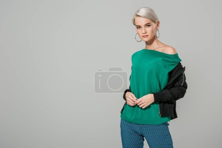 attractive young woman in green sweater posing isolated on grey background