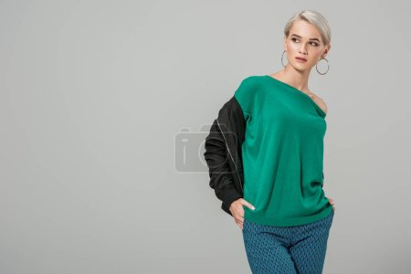 fashionable young woman in stylish outfit looking away isolated on grey background