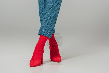 cropped image of female models legs in red stylish boots on grey background