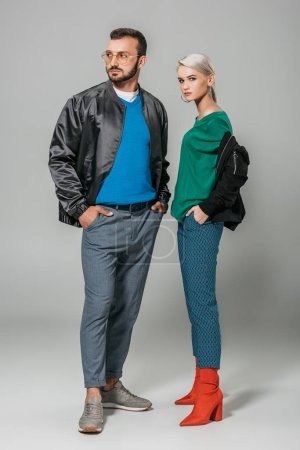 fashionable couple of models in stylish autumn outfits on grey background