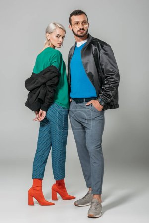 young couple of models in stylish autumn jackets on grey background