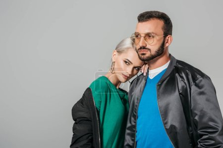 couple of modes in stylish outfits looking away isolated on grey background
