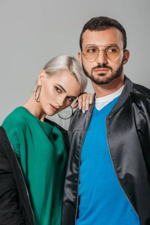 young couple of modes in stylish outfits looking away isolated on grey background