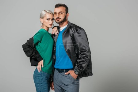 couple of modes in stylish outfits looking at camera isolated on grey background