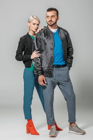 handsome male model in autumn outfit posing near stylish girlfriend on grey background