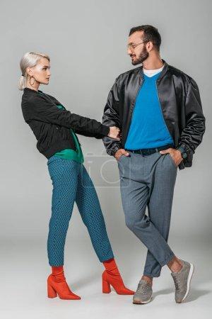 beautiful stylish female model pulling hand of boyfriend on grey background