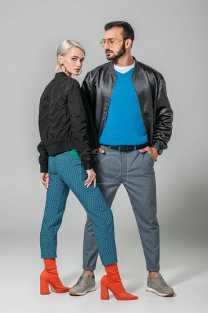 stylish male model posing with hands in pockets near beautiful girlfriend on grey background