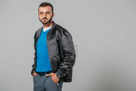 confident man in autumn outfit posing with hands in pockets isolated on grey background