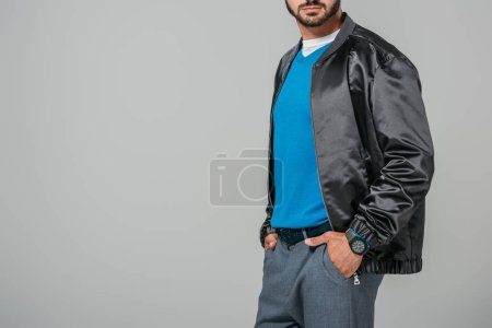 cropped image of man in stylish outfit posing with hands in pockets isolated on grey background