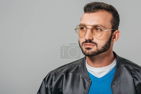 handsome bearded man in stylish eyeglasses looking away isolated on grey background