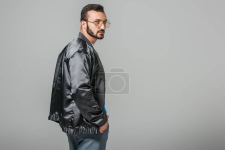 confident handsome man in stylish black bomber isolated on grey background